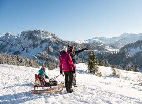 Familienausflug im Winter mit dem Rodel auf präparierten Wanderwegen in den Hörnerdörfern, © Tourismus Hörnerdörfer, F. Kjer