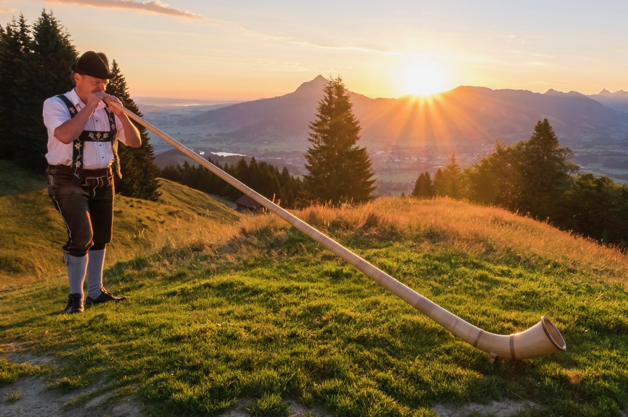 Alphornspieler am Ofterschwanger Horn zum Sonnenaufgang über den Allgäuer Alpen., © Tourismus Hörnerdörfer